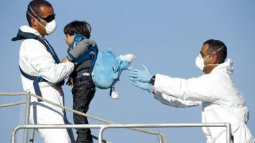 A young immigrant being moved to a rescue ship. © Darrin Zammit-Lupi